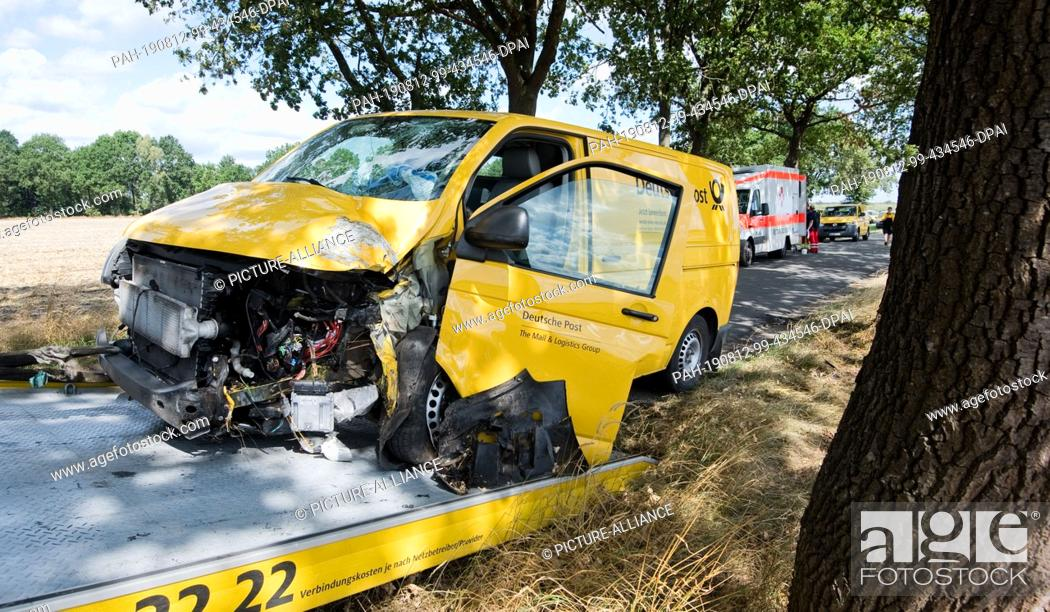 Stock Photo: 12 August 2019, Lower Saxony, Zahrenholz: A Deutsche Post vehicle is towed away on a country road in the Gifhorn district after the vehicle crashed into a tree.