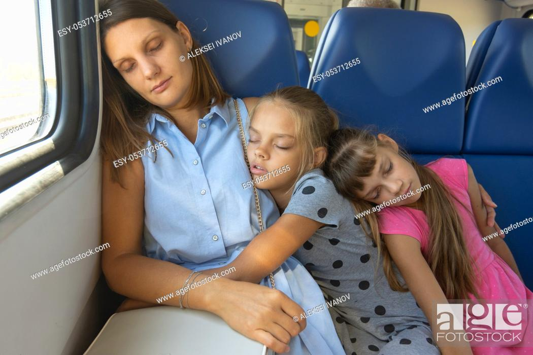 Stock Photo: Mom and two daughters fell asleep in an electric train car.