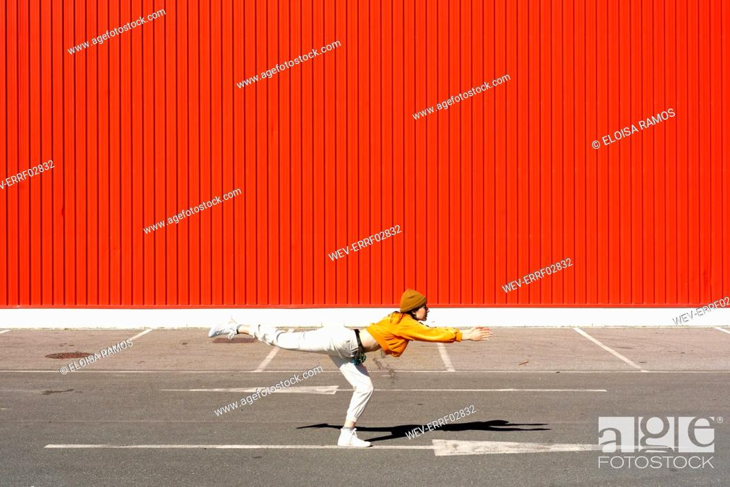 Stock Photo: Young woman dancing in front of a red wall.