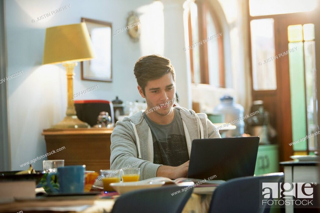 Stock Photo: Young man college student studying at laptop.