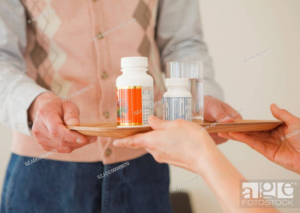 Stock Photo: Senior couple handing over a tray of supplements.
