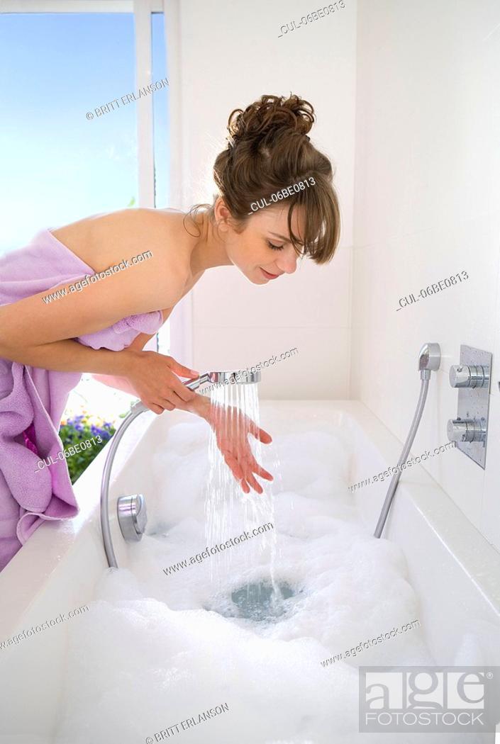 Stock Photo: Woman filling bathtub.