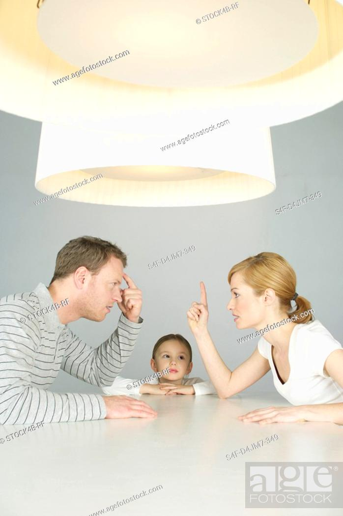 Stock Photo: Couple arguing at table, girl in background.