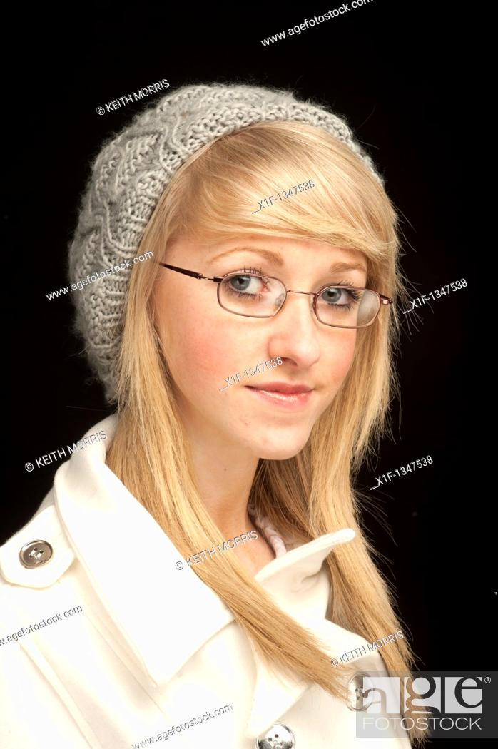 Stock Photo: A slim blonde short-sighted 14 year old teenage girl wearing glasses , UK.