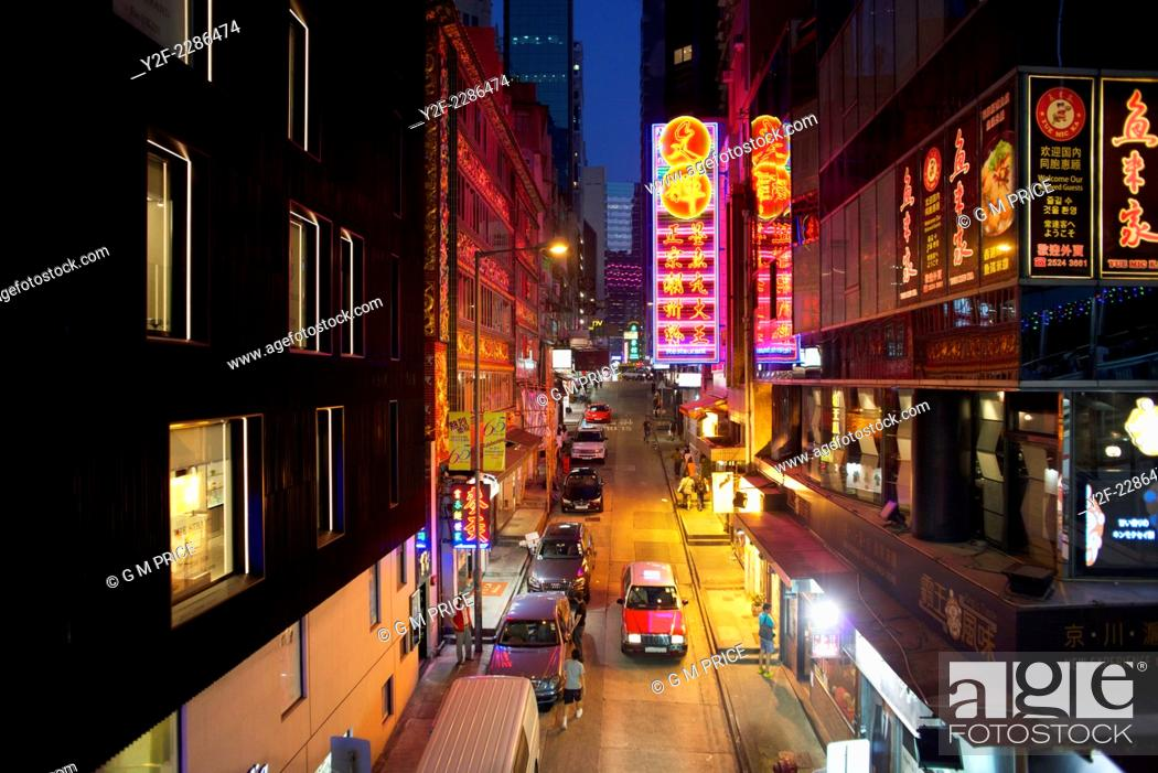 Stock Photo: elevated view of taxi driving through neon lit restaurants and shops in Soho district, Hong Kong.