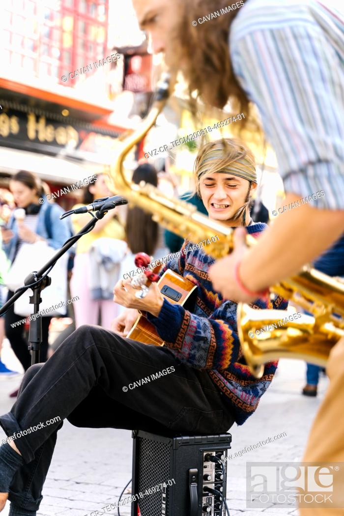 Imagen: Selective focus ont he face of a man singing while playing guitar next to a saxophonist in the street.