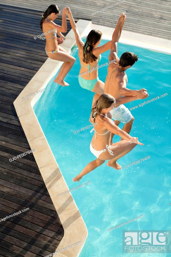 Stock Photo: Friends holding hands jumping into swimming pool.