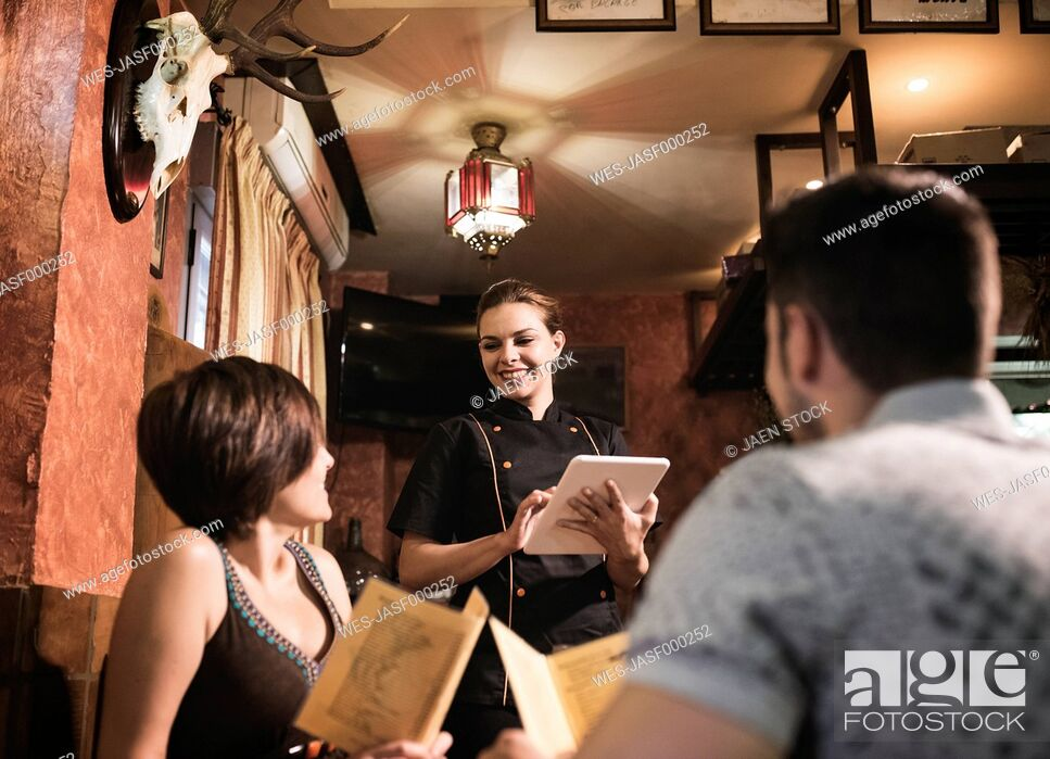 Stock Photo: Couple in restaurant with waitress taking the order.