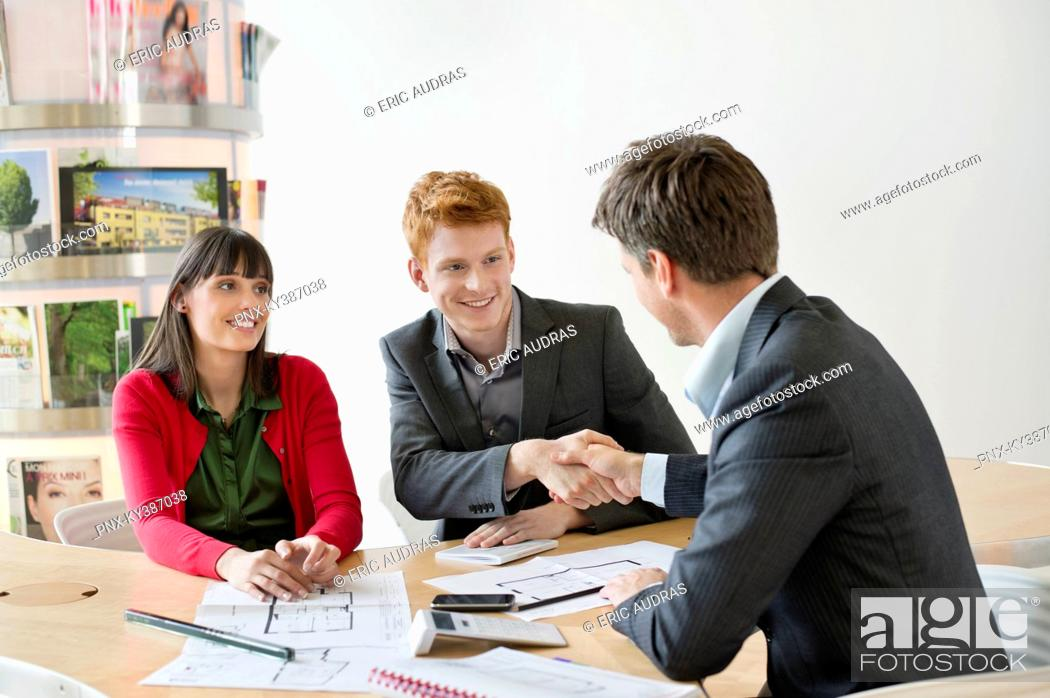 Stock Photo: Real estate agent discussing property documents to his clients.