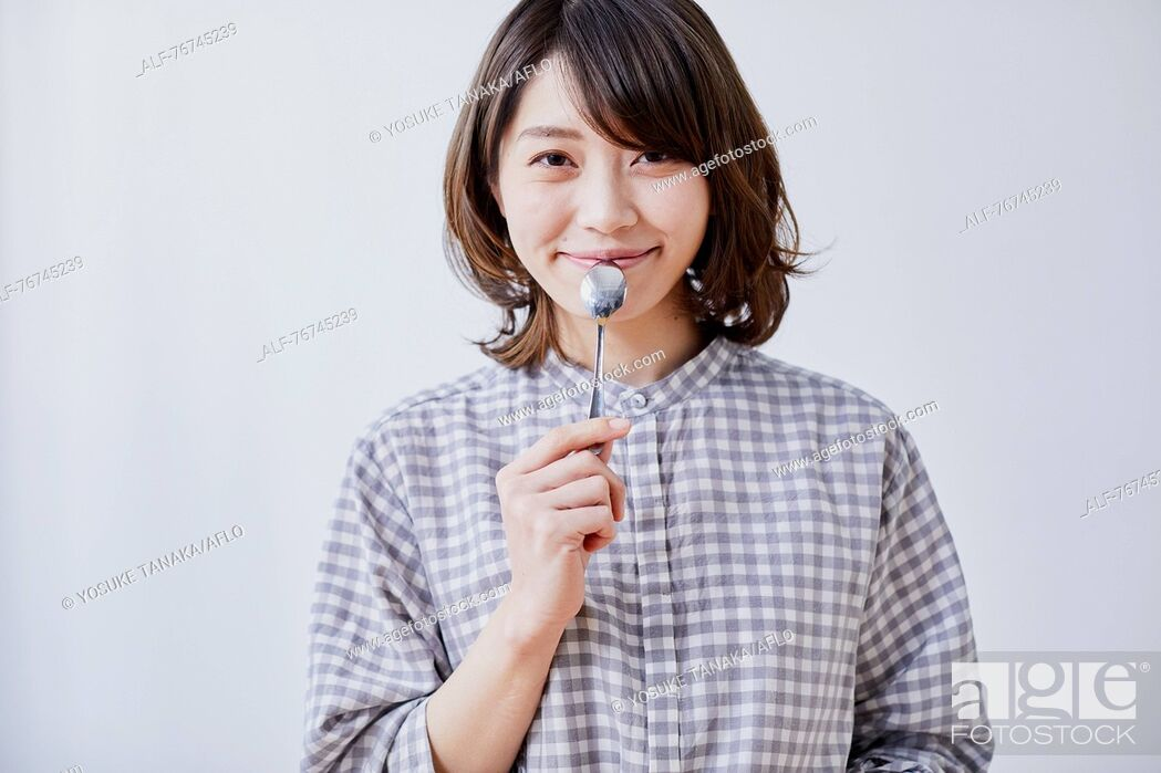 Stock Photo: Young Japanese woman eating cake.