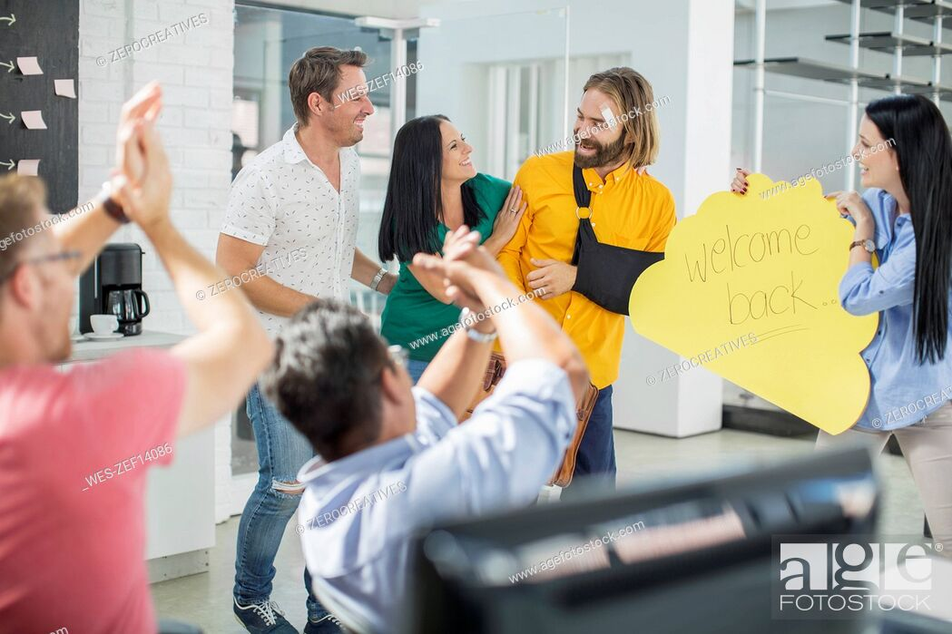 Stock Photo: Colleagues cheering and welcoming injured friend back.