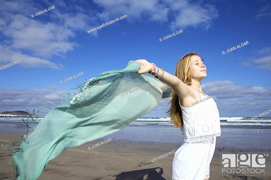 Stock Photo: Happy young woman with beach wrap running at the seacoast. Horizontal outdoors shot.