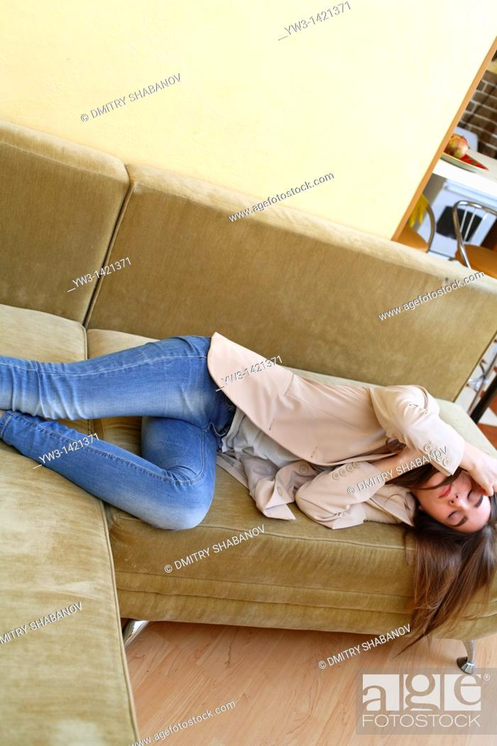 Stock Photo: Young woman in jeans sleeping on sofa.