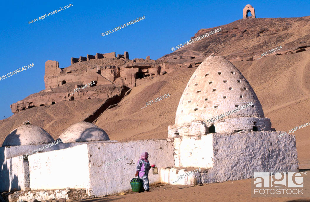 Stock Photo: Grave of a holy man and young camel driver passing by, village of Gharb Aswan on west bank near Aswan. Nubia, Egypt.