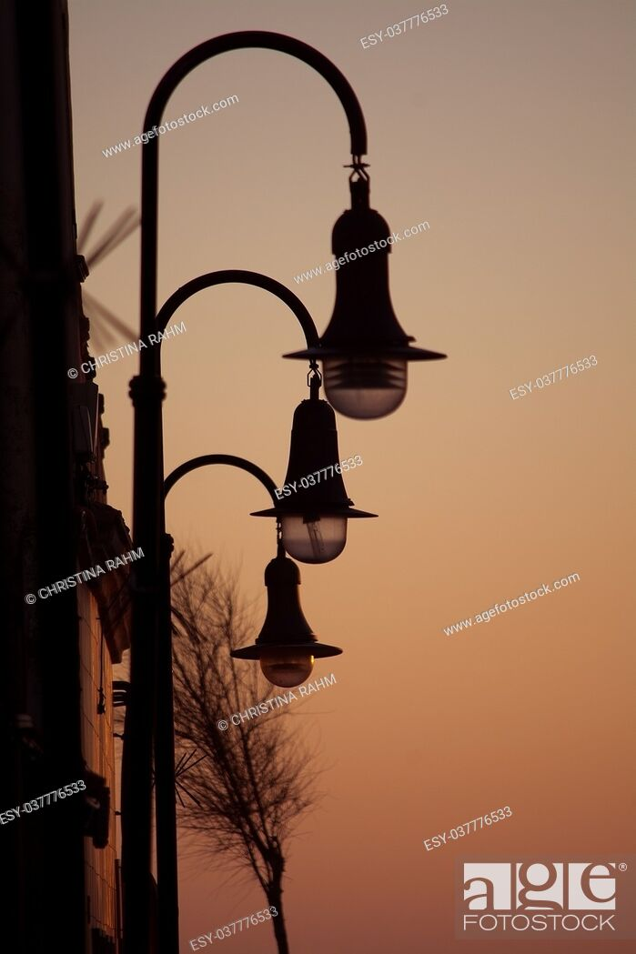 Stock Photo: Retro streetlights and evening golden sky mood background.