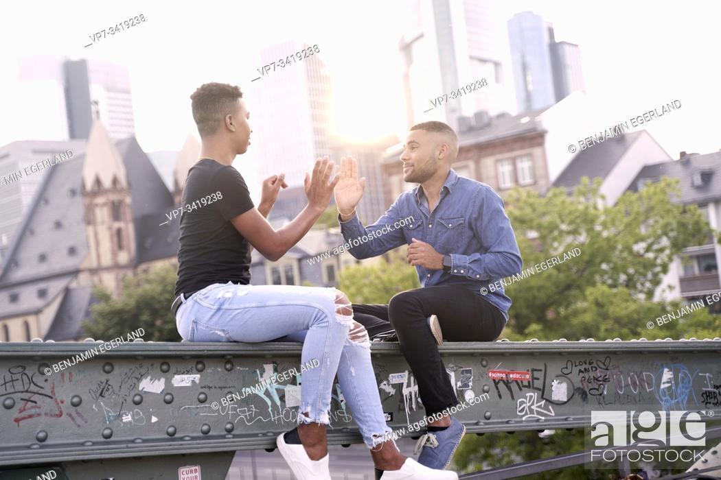 Stock Photo: Gay couple sitting on bridge structure, playing patty cake game. Frankfurt, Germany.