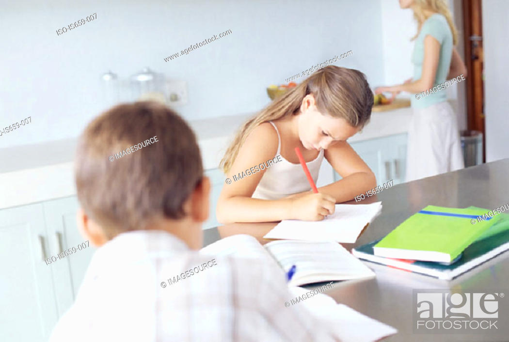 Stock Photo: Children doing homework in the kitchen.