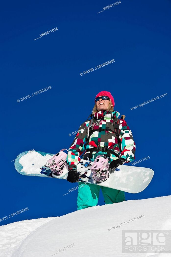 Stock Photo: A snowboarder looks out over the snowy mountains with joy.