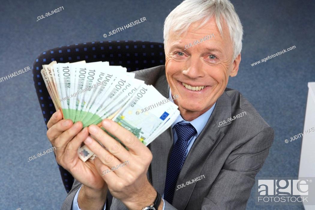 Stock Photo: Businessman holding money, smiling.