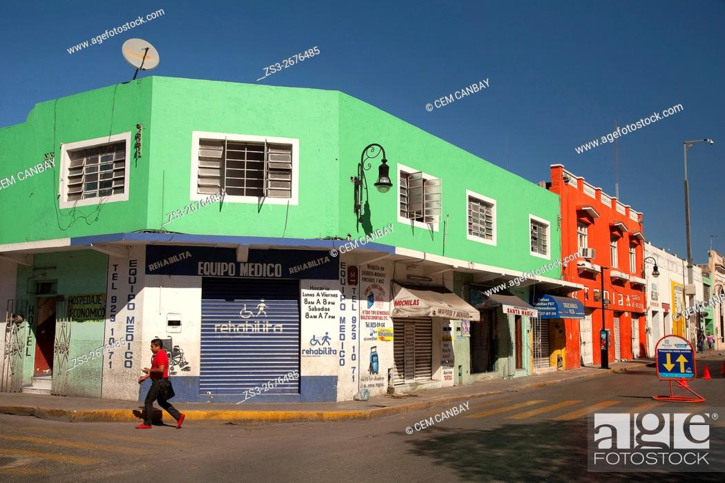 Stock Photo: Man walking in front of the colorful colonial buildings in city center, Merida, Yucatan Province, Mexico, Central America.