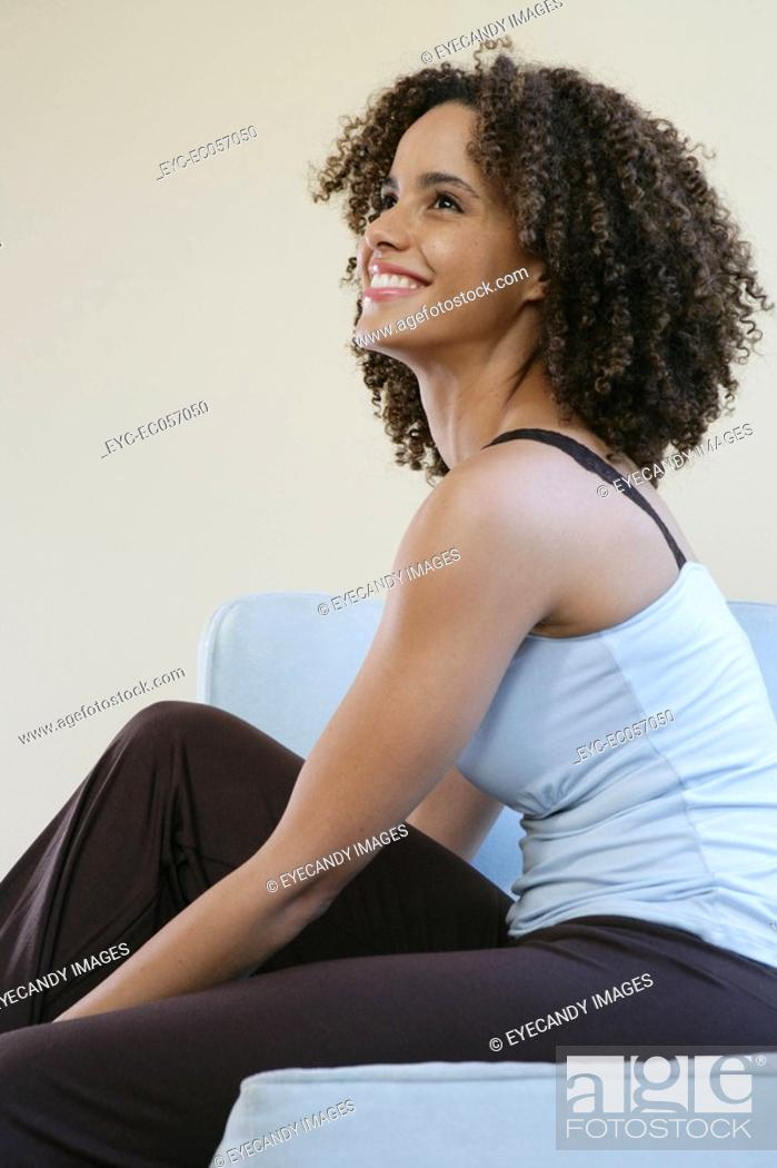 Stock Photo: Young woman seated, looking up.