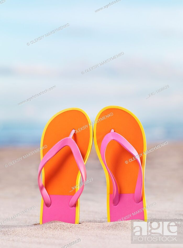 Imagen: Close up of a pair of bright orange flip flops at the beach under blue sky background.