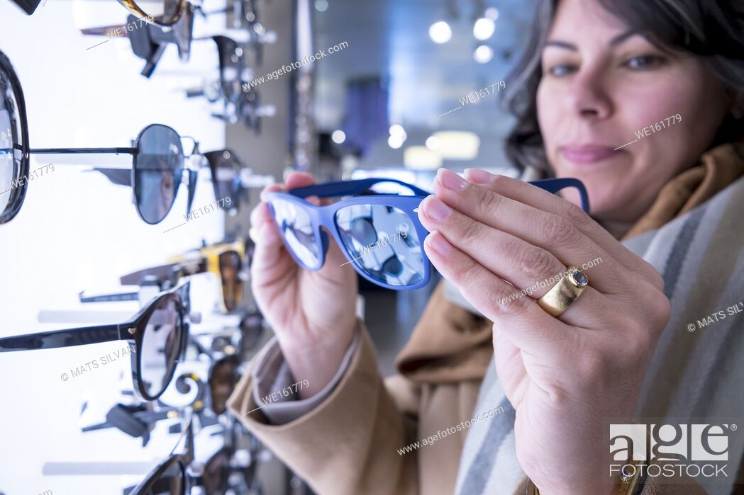 Stock Photo: Woman Holding a Pair of Sunglasses in Retail Store.
