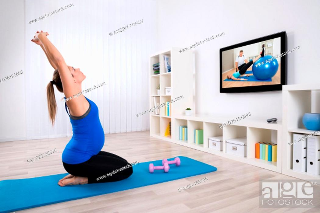 Stock Photo: Young Pregnant Woman Exercising In Front Of Television At Home.