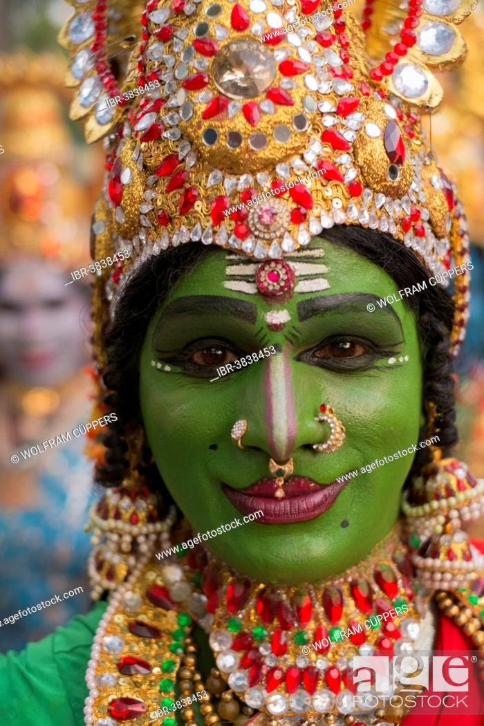 Hindu temple dancer wearing gold jewelry with his face painted green