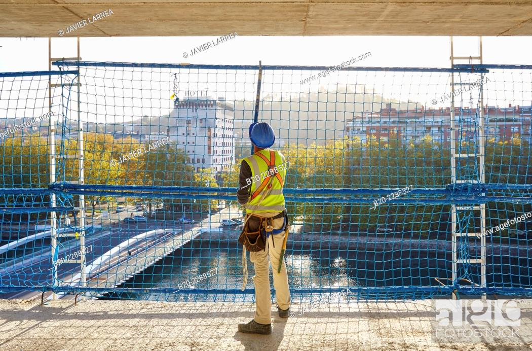 Imagen: Worker placing Security System Work RESA. Protection in building work in construction. System that eliminates the possibility of people falling in the works.