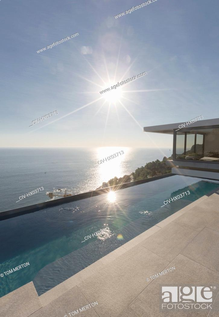 Stock Photo: View of sun shining over ocean and modern, luxury home showcase exterior lap pool patio.