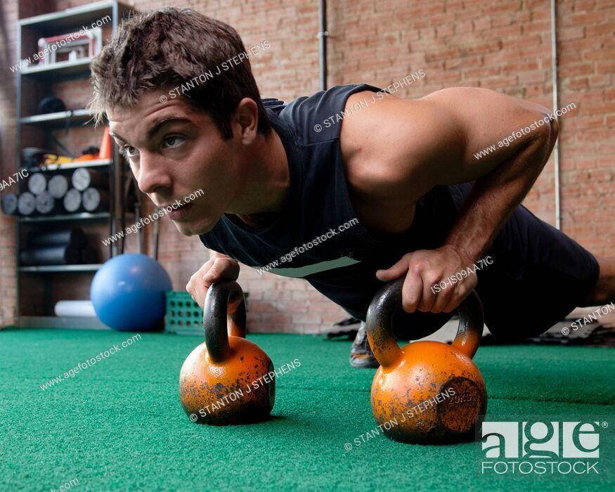 Stock Photo: Male bodybuilder doing press up using kettlebells.