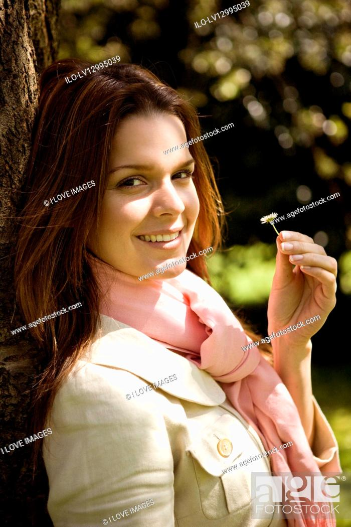 Stock Photo: A young woman holding a daisy, smiling.