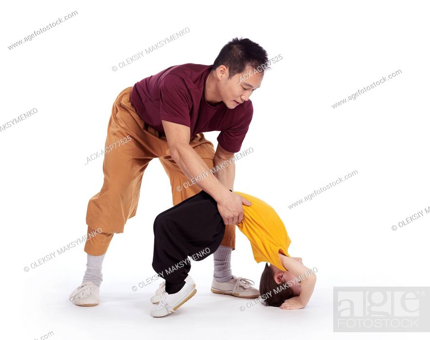 Imagen: Martial art instructor helping a child to hold a bridge stand isolated on white background.