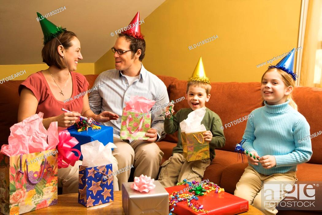 Stock Photo: Caucasian family wearing party hats and celebrating a birthday party.
