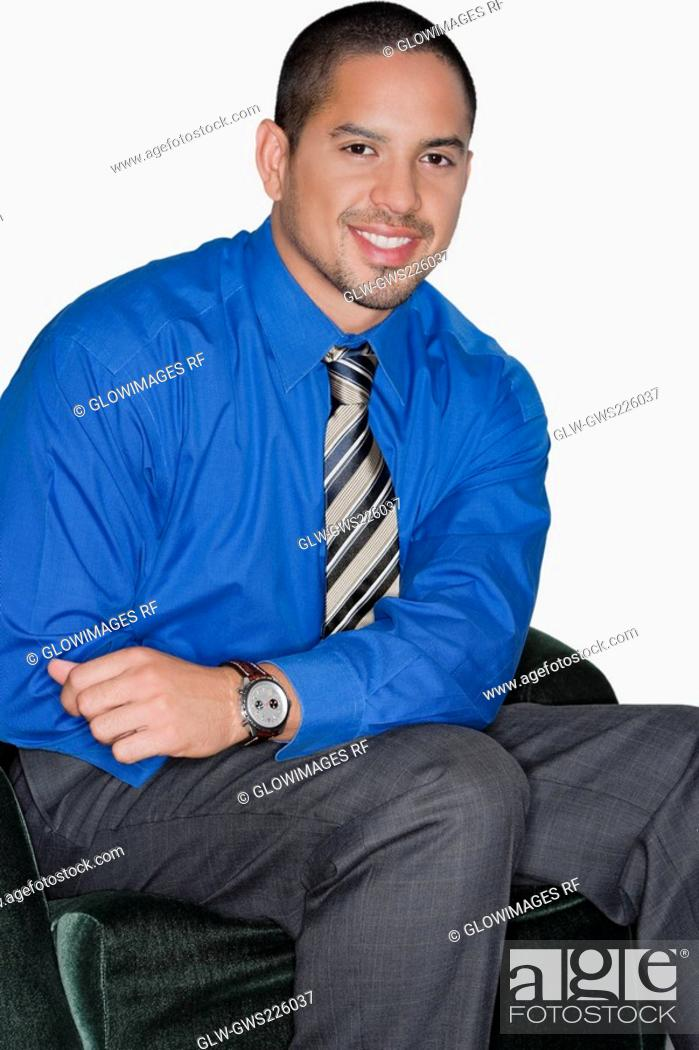 Stock Photo: Portrait of a businessman sitting on a chair and smiling.