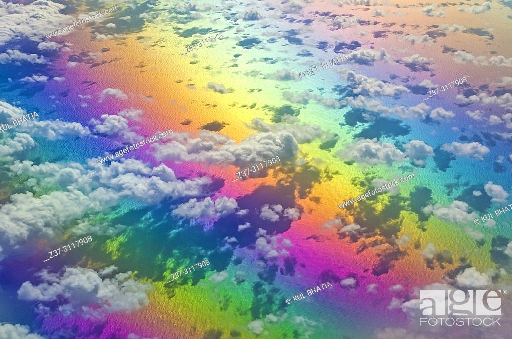 Photo de stock: Aerial view of clouds below, at 10,000 meters, photographed from a regular commercial flight. The rainbow of colours is due to light refraction.