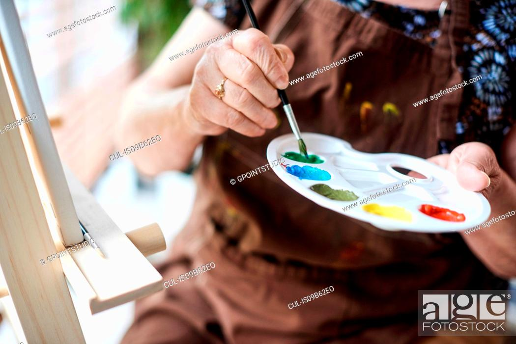 Stock Photo: Woman holding palette with brush and paints.