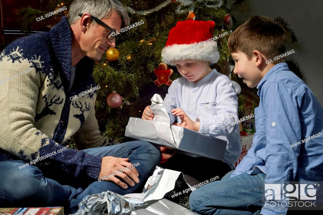 Stock Photo: Father on sitting room floor opening christmas gifts with two sons.