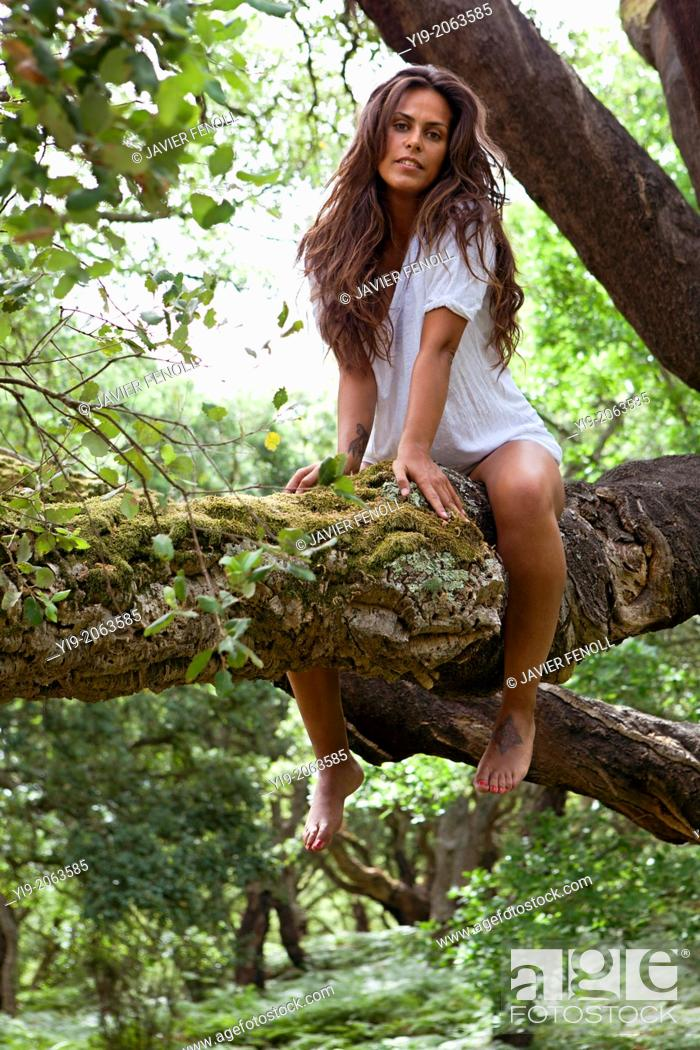Stock Photo: Fashion portrait of young sensual lady on tree.