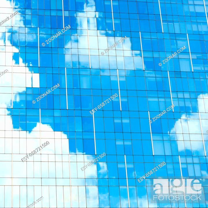Stock Photo: Blue sky and white clouds reflection on glass facade of a modern office building.