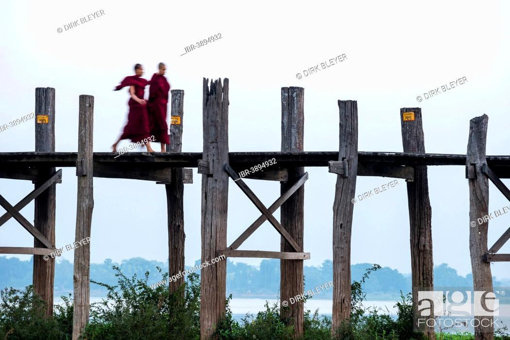 Stock Photo: Monks walking on a teak bridge, U Bein Bridge, across Thaungthaman lake, Amarapura, Mandalay Division, Myanmar.