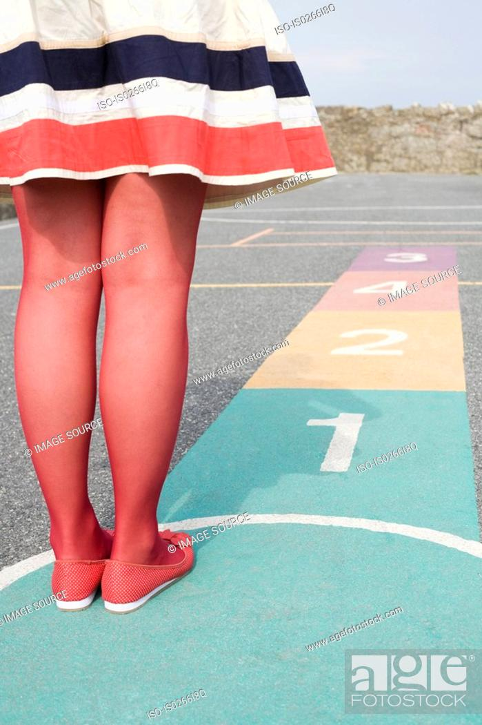 Stock Photo: Young woman playing hopscotch.