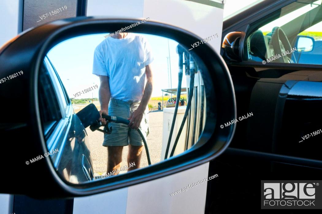 Stock Photo: Man holding gas pistol, refuelling at a gas station.