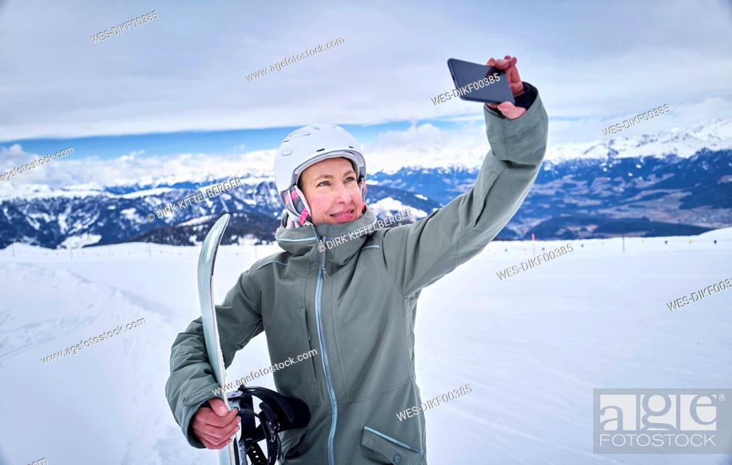 Stock Photo: Smiling female snowboard taking a selfie with her smartphone.