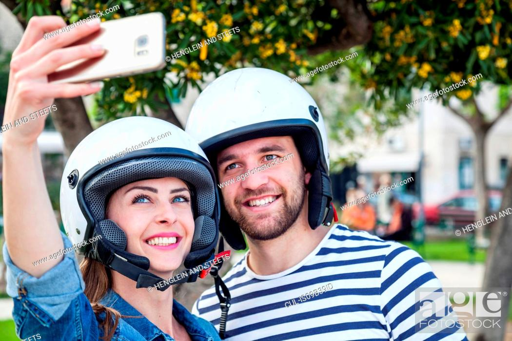 Stock Photo: Young moped couple taking selfie in park, Split, Dalmatia, Croatia.