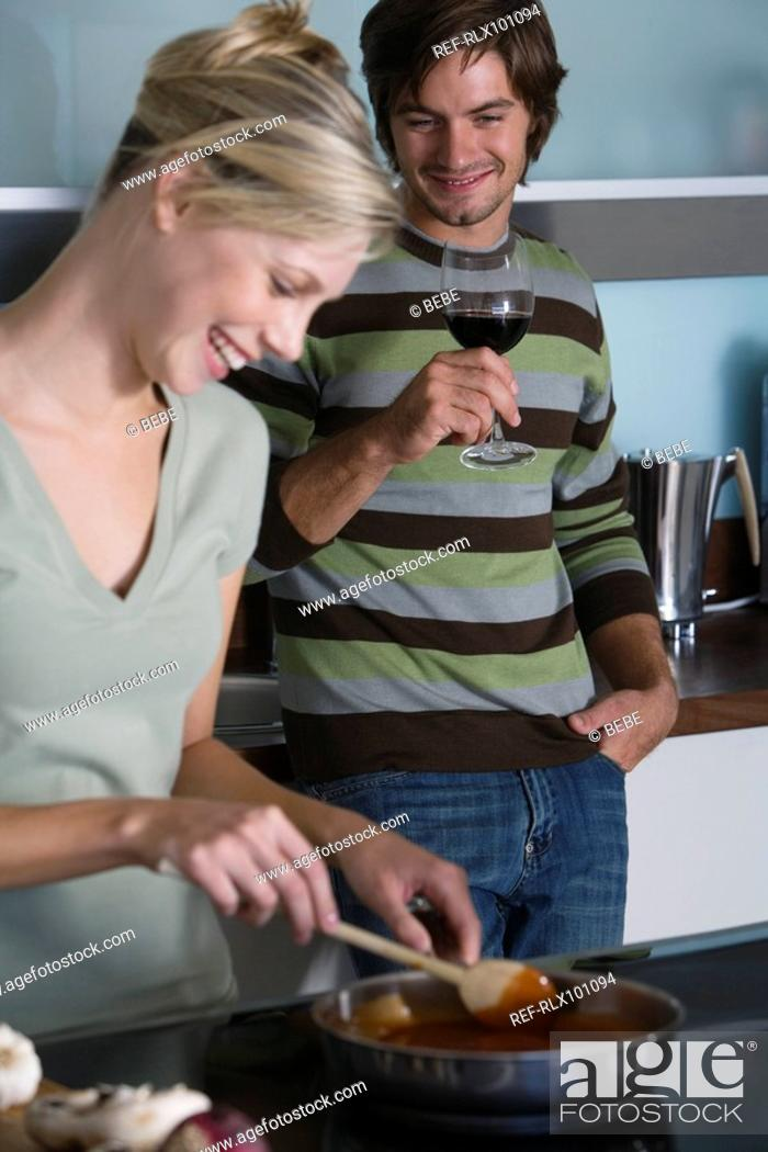 Stock Photo: Young couple in modern kitchen, cooking together, smiling, drinking red wine.