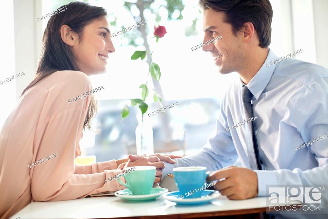 Stock Photo: Smiling couple holding hands and drinking coffee in café.
