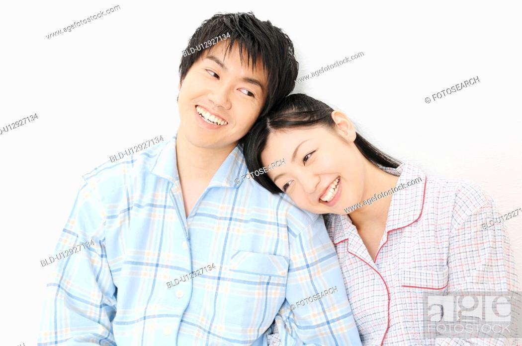 Stock Photo: Couple putting on pjamas.