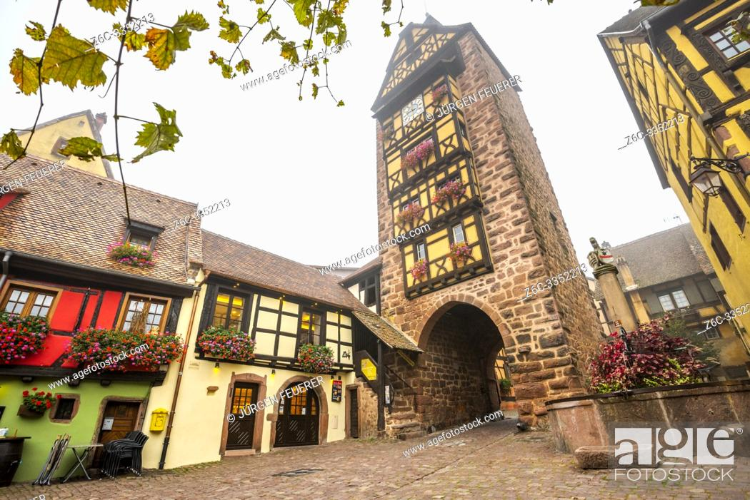Stock Photo: old town gate of the village Riquewihr with timberwork, Alsace Wine Route, France, the landmark Dolder tower and flower-bedecked well.